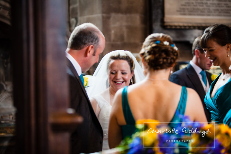 bride laughing with the groom while family members sign the registar