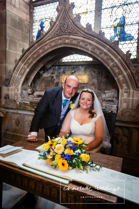bride and groom posed in st. alkmunds church after signing the registar looking at the camera