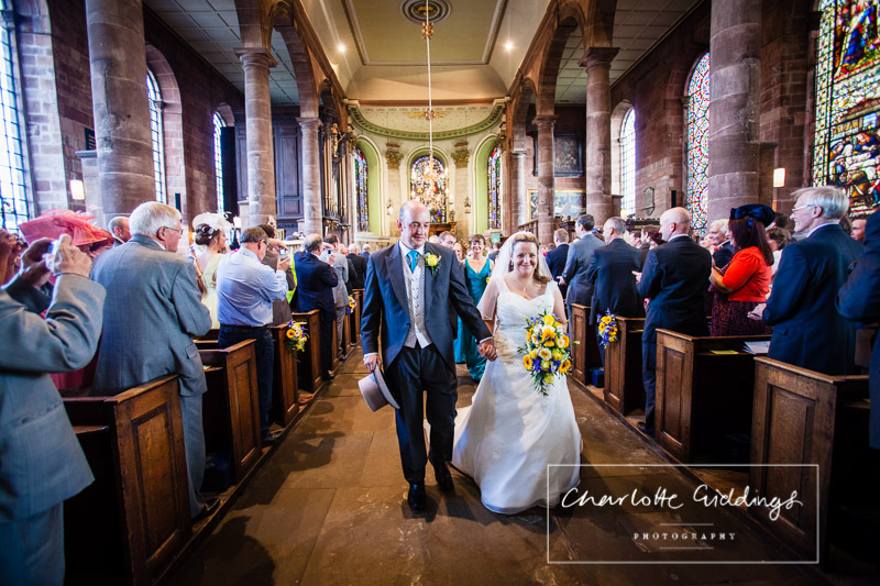 bride and groom now mr and mrs looking delighted walking down the aisle at st. alkmunds church - wedding photographer shropshire