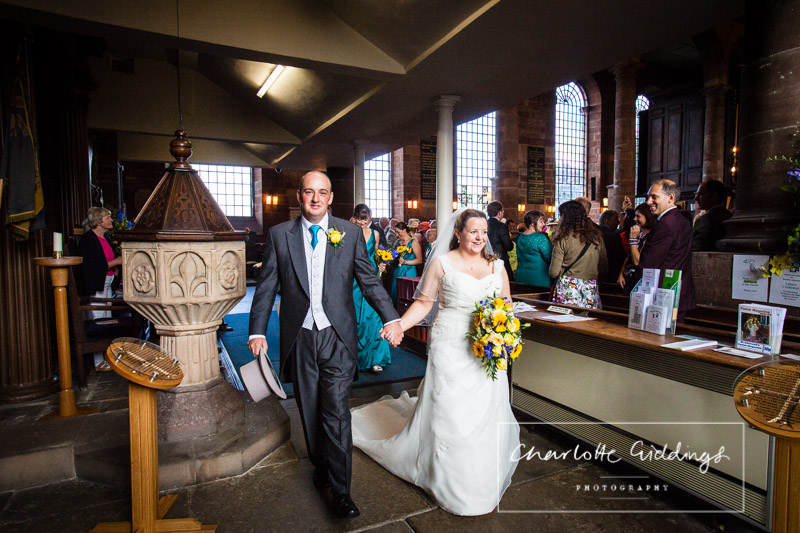 bride and groom walking towards the front entrance of the church - shropshire wedding photographer
