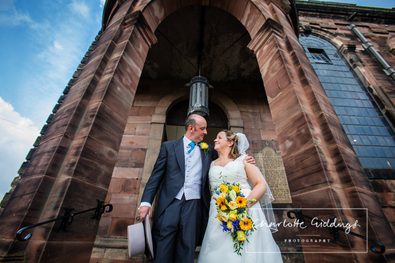bride and groom looking at one another while standing in the church door way and beautiful blue sky