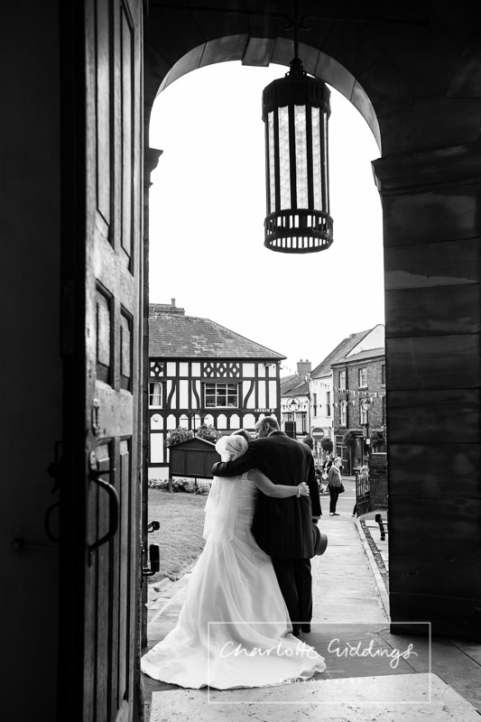 black and white photo of bride and broom having a kiss in st alkmunds church doorway taken from inside the church