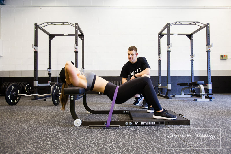 coach dan assisting client while doing resistance hip thrusts - shropshire photographer