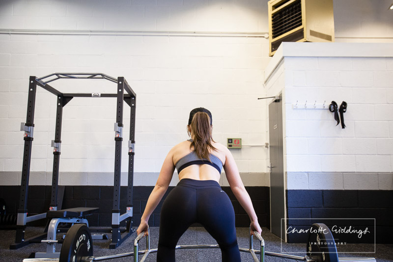 client squatting to lift dead weight on the bar, shot from the back