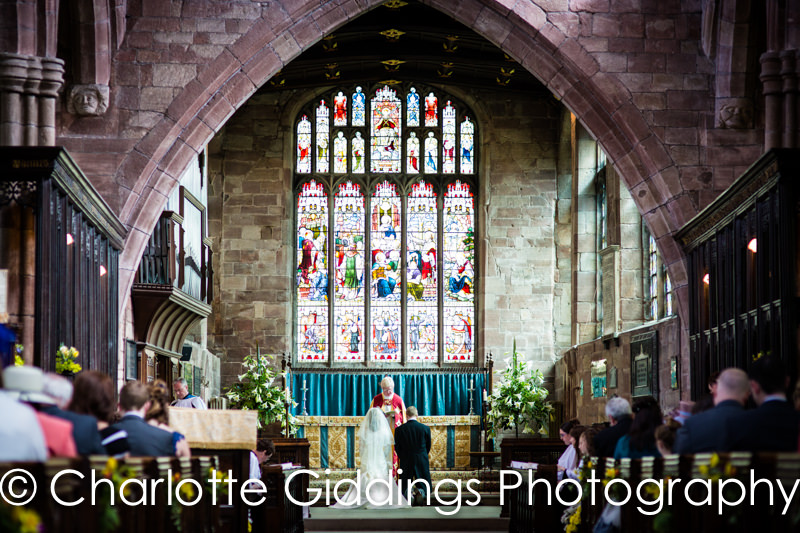 wide shot of the bride and groom at the alter in st.oswalds church malpas
