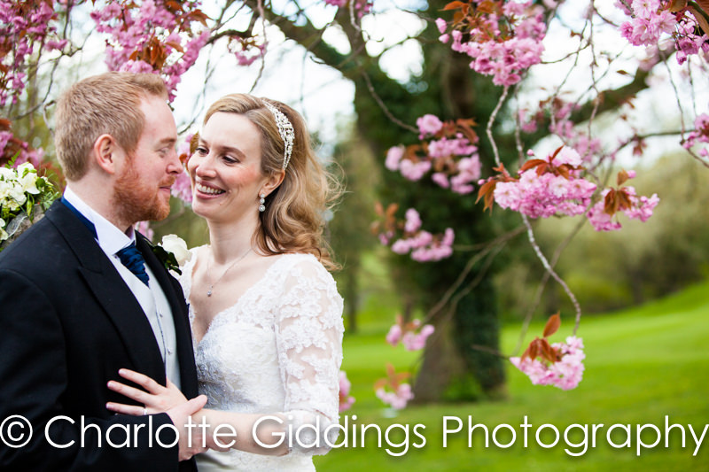 bride and groom looking at each other adoringly amongst the cherry blossom - hill valley wedding photographer