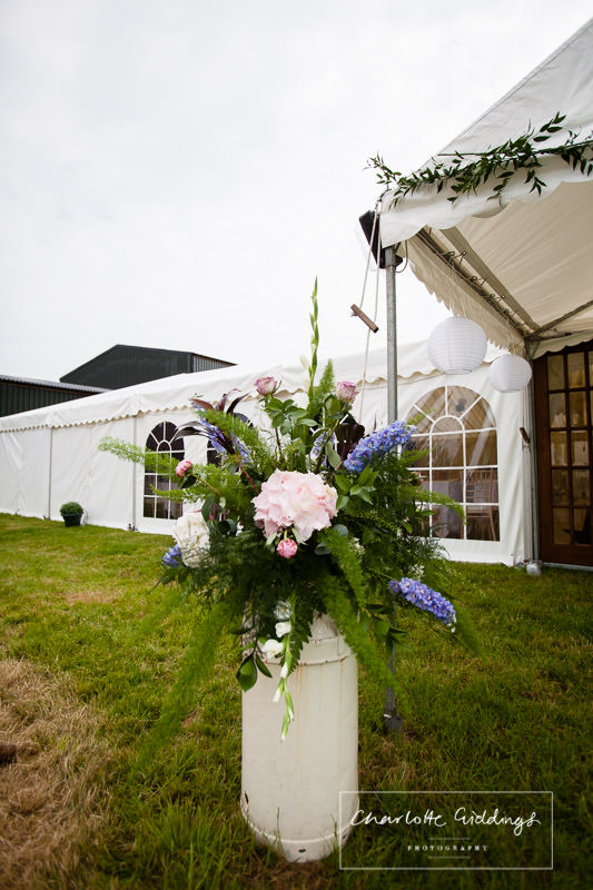 marquee decor - summer flowers in milk churn outsdei marquee