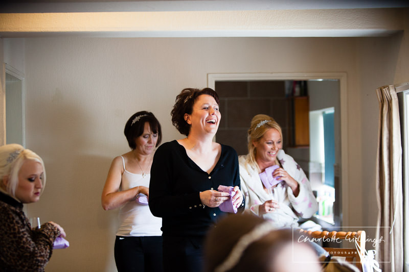 bridesmaid opening gift from bride and laughing out loud - shropshire wedding photographer