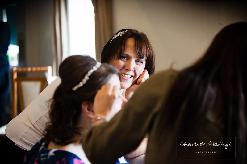 bridesmaid looking at bride having makeup done during bridal prep at home