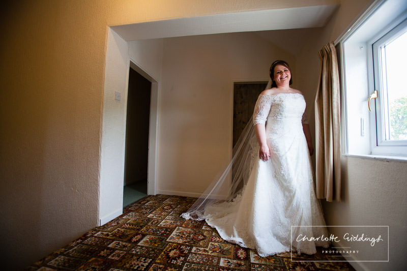 full length shot  of the bride in natural light at home, ready to go to bronington church, wales