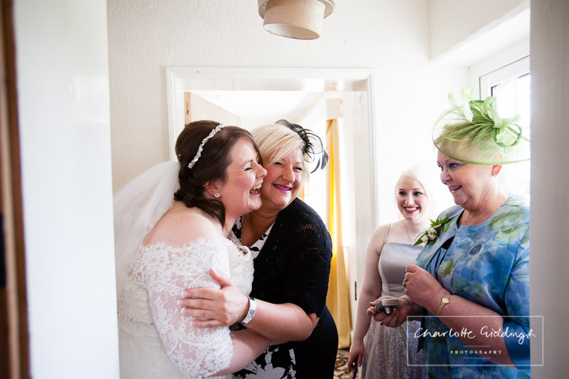 bride and friend very excited to see one another, ready to go to church - shropshire wedding photographer