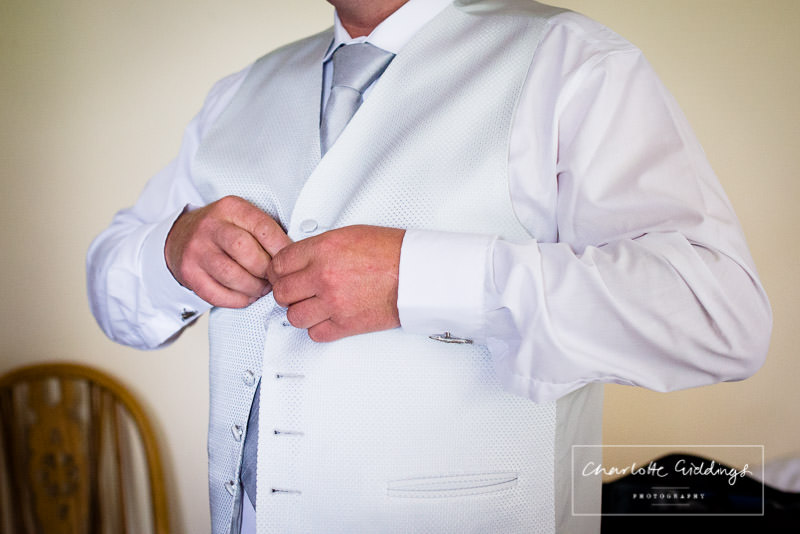 detail shot of the groom doing the buttons on his waistcoat - charlotte giddings photography