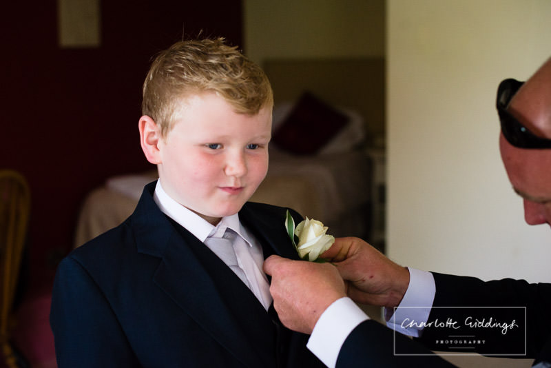 groom putting his son's button hole on his jacket - wedding photographer wales - charlotte giddings photography