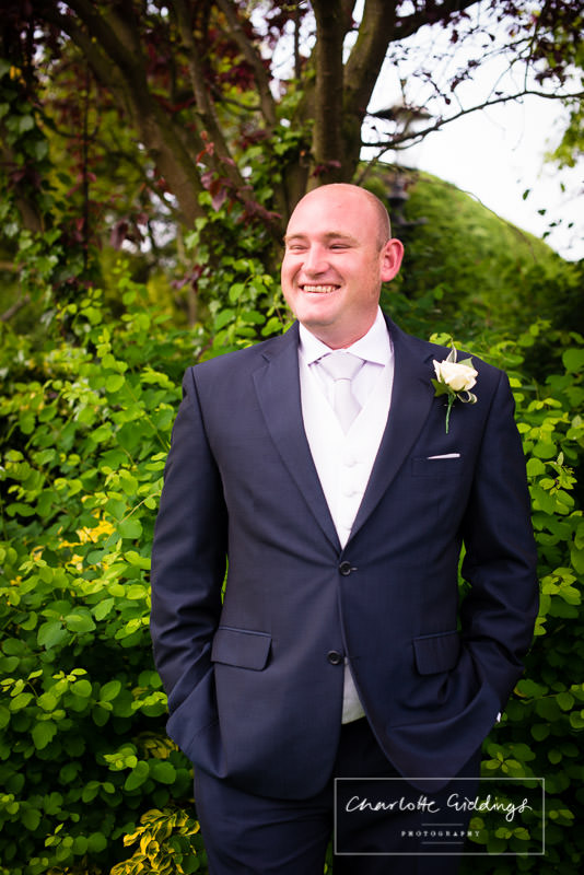 portrait of the groom looking very happy before he leaves for bronington church, charlotte giddings photography
