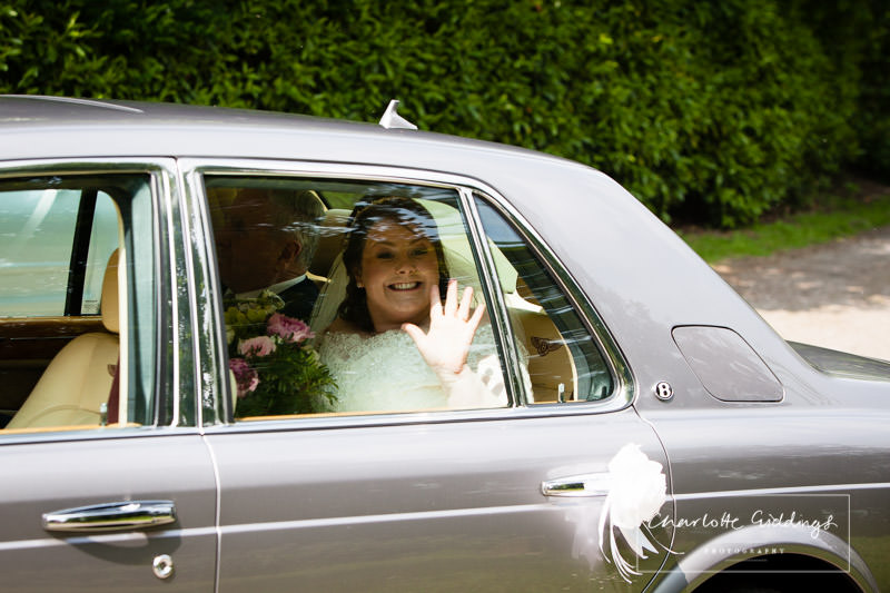 very excited bride waving out of the window as she arrives at bronington church