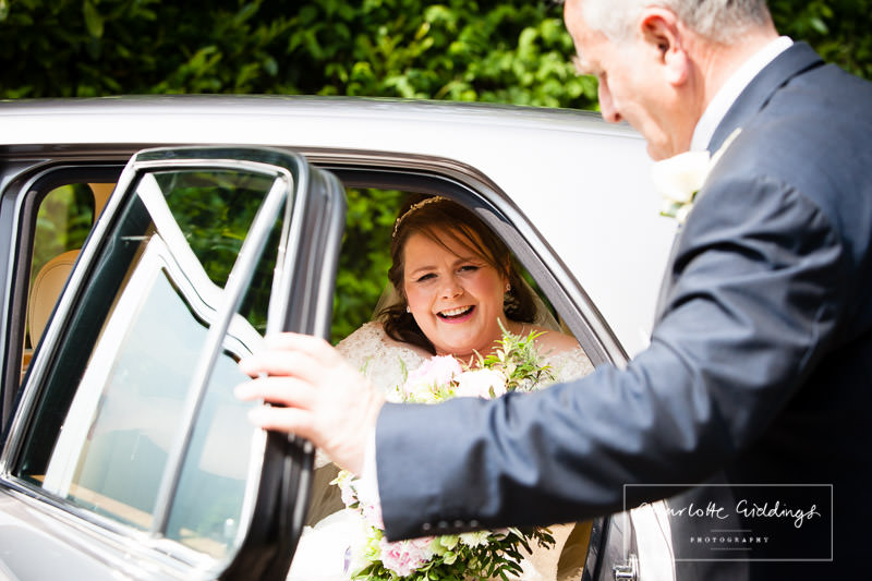 father of the bride opening the door for bride at bronington church wedding, wales