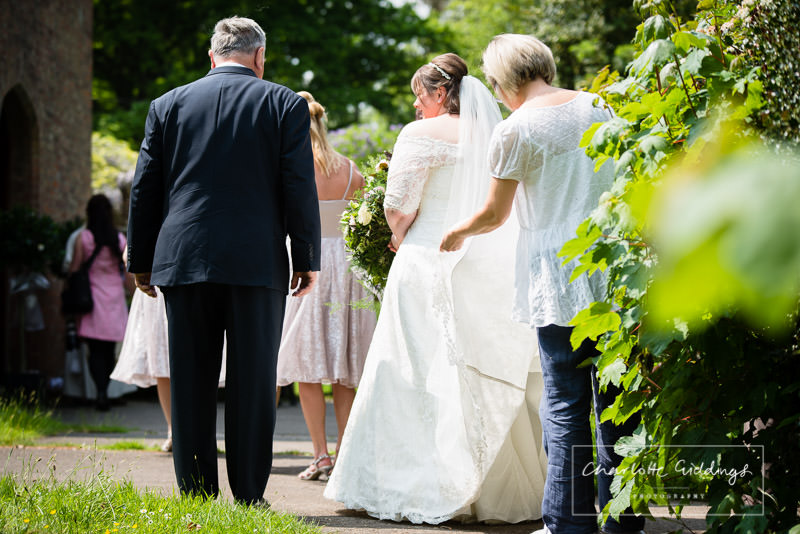 guest helping bride with her dress as she enters bronington church, shropshire wedding photographer