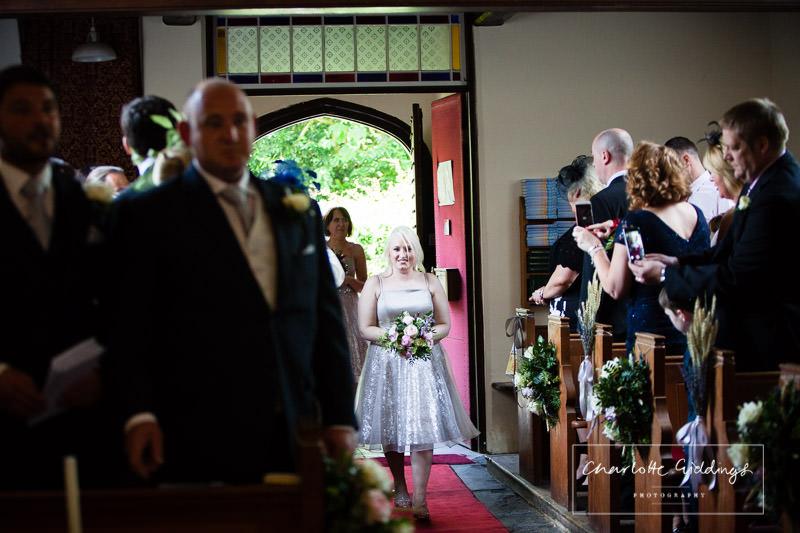 bridesmaid walking down the aisle in bronington church - wedding photographer shropshire