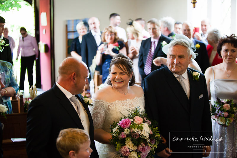 bride and groom and father of the bride exchanging smiles seeing each other for the first time on their wedding day at bronington church , wales wedding photographer