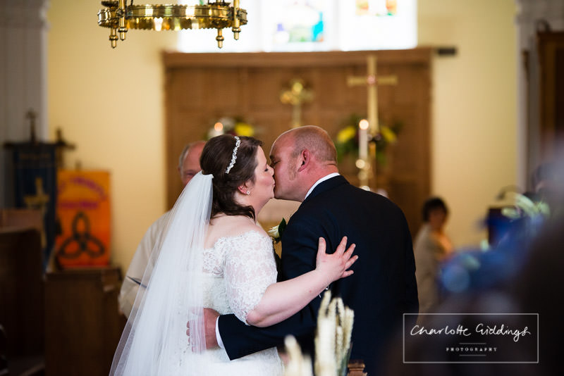 bride and groom kissing in bronington church wedding ceremony taken from the back of church - wedding photographer shropshire