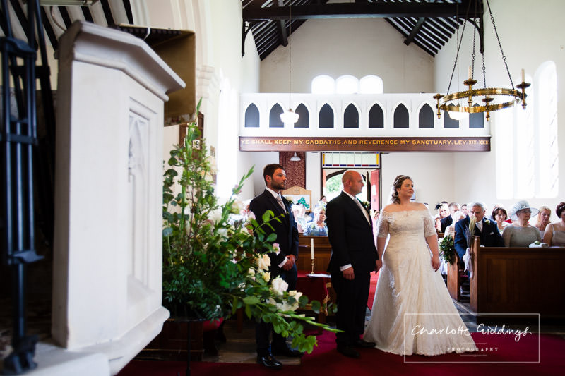 bride groom and best man listening to the vicar talking in bronington church wedding ceremony