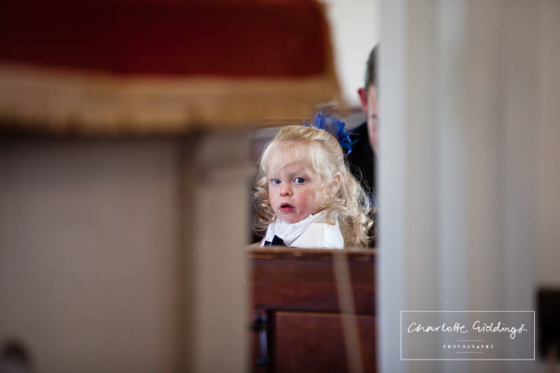 candid photo of a curious little girl during church wedding ceremony bronington church wales