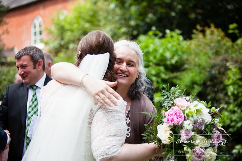 friend congratulating the bride outside church - wedding in wales bronington church