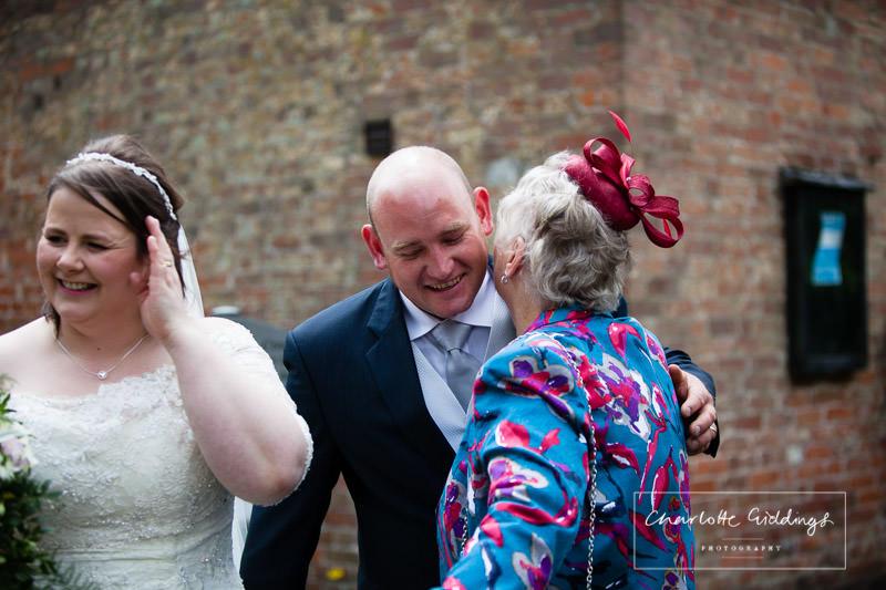 groom greeting guests outside bronington church - shropshire wedding photographer
