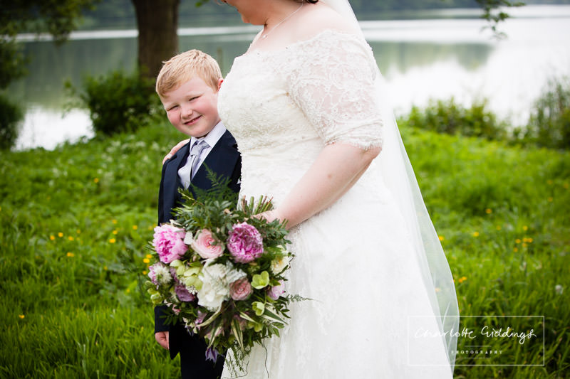 bride's son looking at the camera while standing next to his mum the bride - shropshire wedding photographer