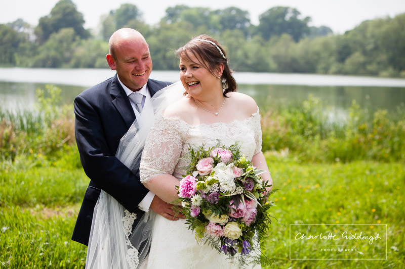 bride and groom laughing with each other at hanmer mere - wedding photographer wales