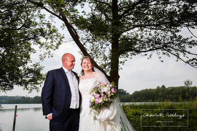 groom looking at his beautiful bride at hanmer mere - shropshire photographer