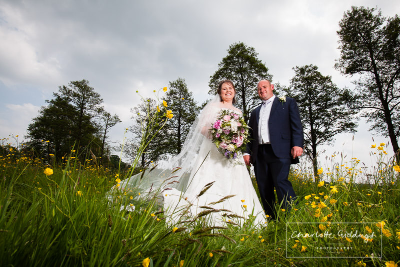 bride and groom portrait full length amongst the buttercups at hanmer mere