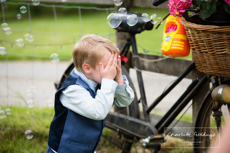 little boy playing hide and seek with bubble gun - candid moment charlotte giddings photography
