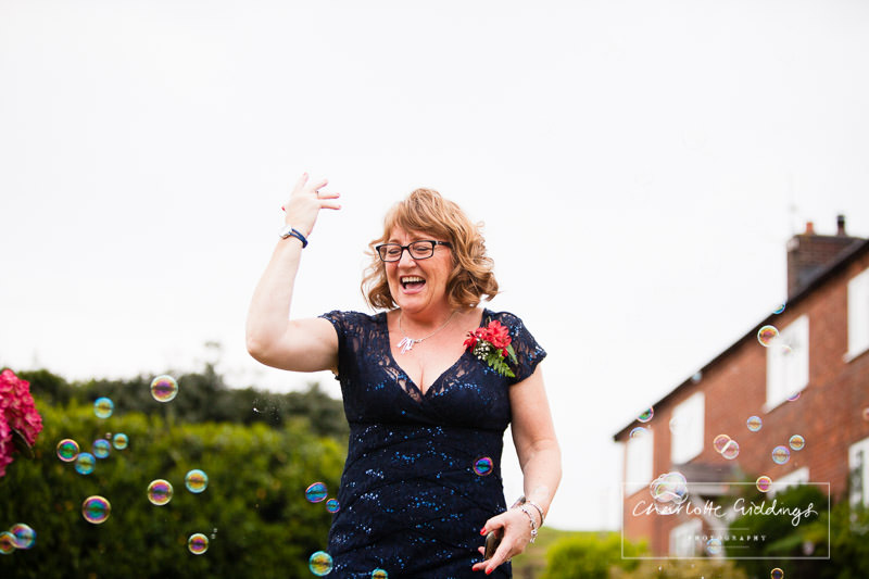 wedding guest playing with bubbles at marquee wedding reception - charlotte giddings photography