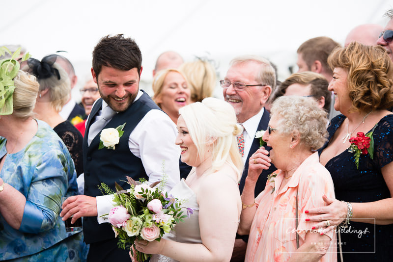 guests laughing during whole group photo - wales wedding - charlotte giddings photography