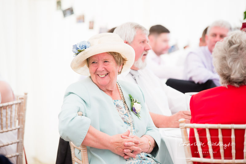 natural photo of guest smiling while sat in the marquee wedding reception - charlotte giddings photography