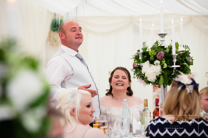groom making his speech and bride smiling - charlotte giddings photography