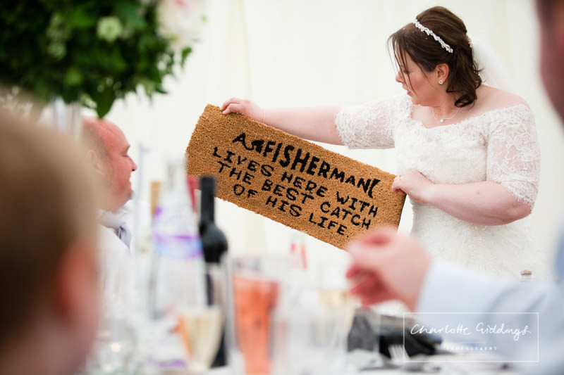 bride presenting a gift to her new husband - a fisherman lives here with the best catch of his life - shropshire photographer