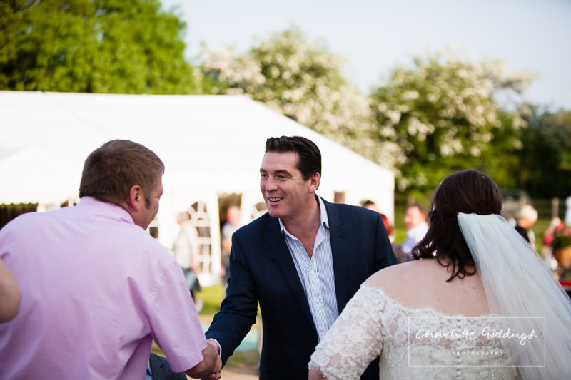 guest arriving for evening do and shaking hands with another guest - charlotte giddings photography