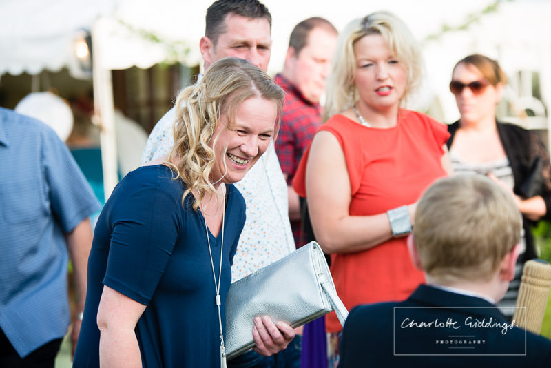 female guest laughing with child at evening celebrations at wales marquee wedding