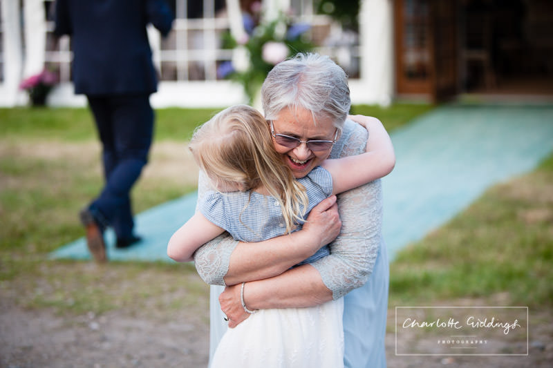 mother of the bride giving a little girl a huge cuddle - charlotte giddings photography