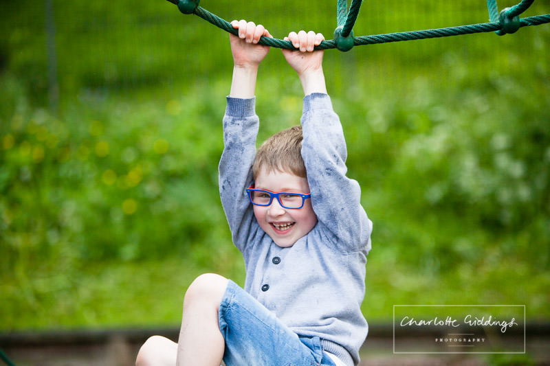 young boy hanging on rope with a beaming smiling - shropshire portrait photographer