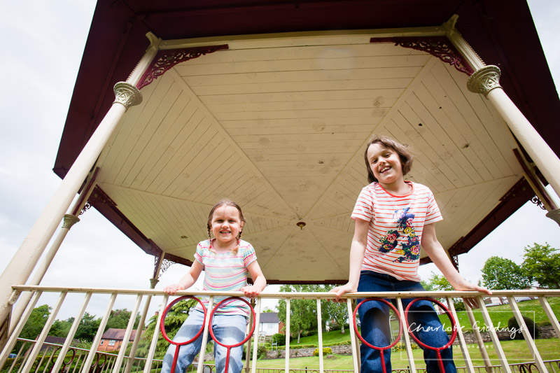two girls on the railings of the bandstand in whitchurch jubilee park, family shoot