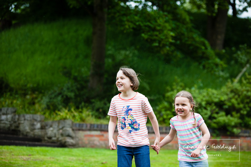 two sisters holding hands looking over towards mum and dad - shropshire portrait photographer