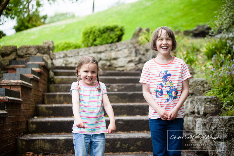 two sisters standing on the steps in jubilee park smiling at one another - charlotte giddings photographer