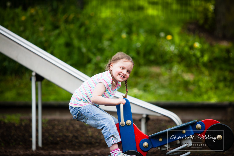 little girl on a rocker smiling towards the camera - jubilee park whitchurch