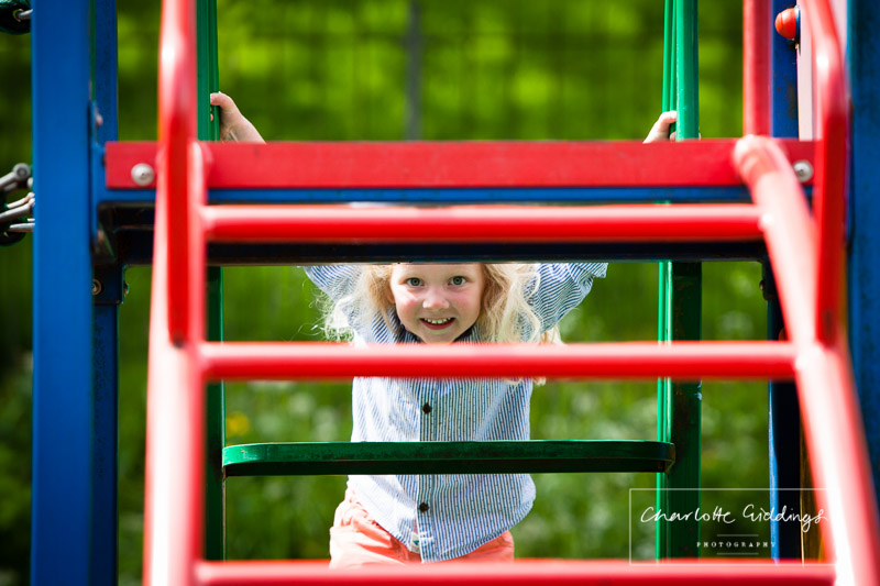 young girl peaking through the ladder of the climbing frame on the park - shropshire portrait photographer