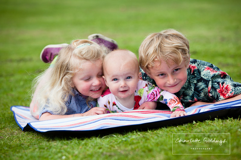 brother and sister lying on a picnic blanket in jubilee park smiling at the camera - charlotte giddings photography