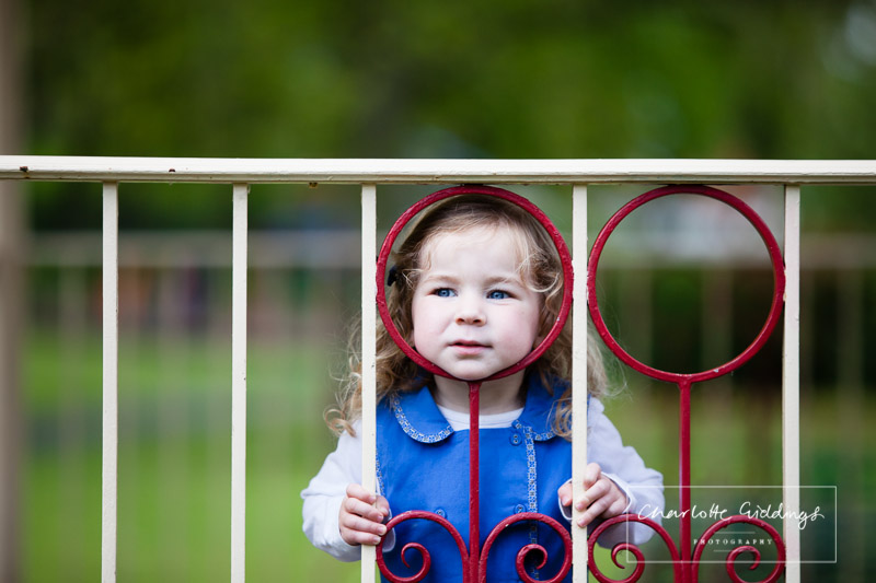 little girl resting her head again a circular shape in the railings - shropshire portrait photographer