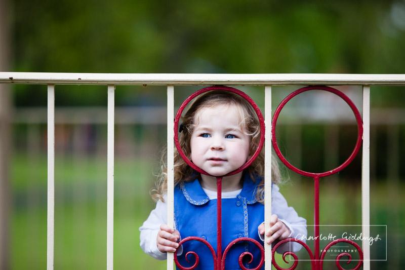 little girl resting her head again a circular shape in the railings - shropshire portrait photographer